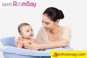 Khi bé bị rôm sảy mẹ nên vệ sinh và mặc thoáng, kiểm tra trên da bé có nhiều chất nhờn không thì tắm qua cho bé